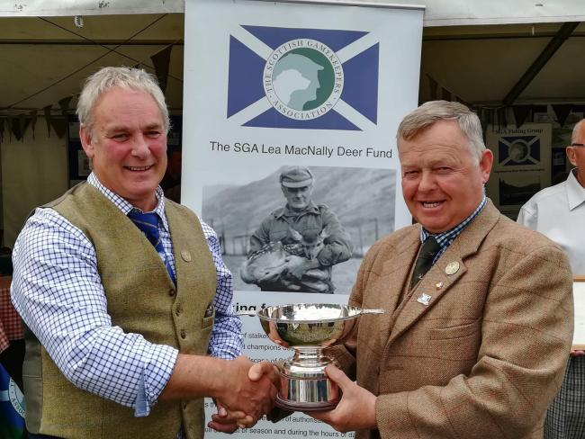 Scottish Gamekeepers Association chairman Alex Hogg (left) presents the Ronnie Rose award to Brian Lyall at Moy Highland Field Sports Fair