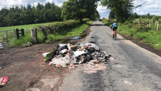 Builders' rubble dumped on the road in front of a field entrace in Lanarkshire