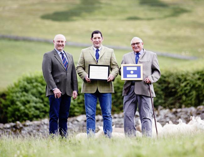 Father and son duo Willie and Jimmy Thomson from Hownam Grange in Kelso recieve the Sir William Young Award from RHASS chairman Bill Gray