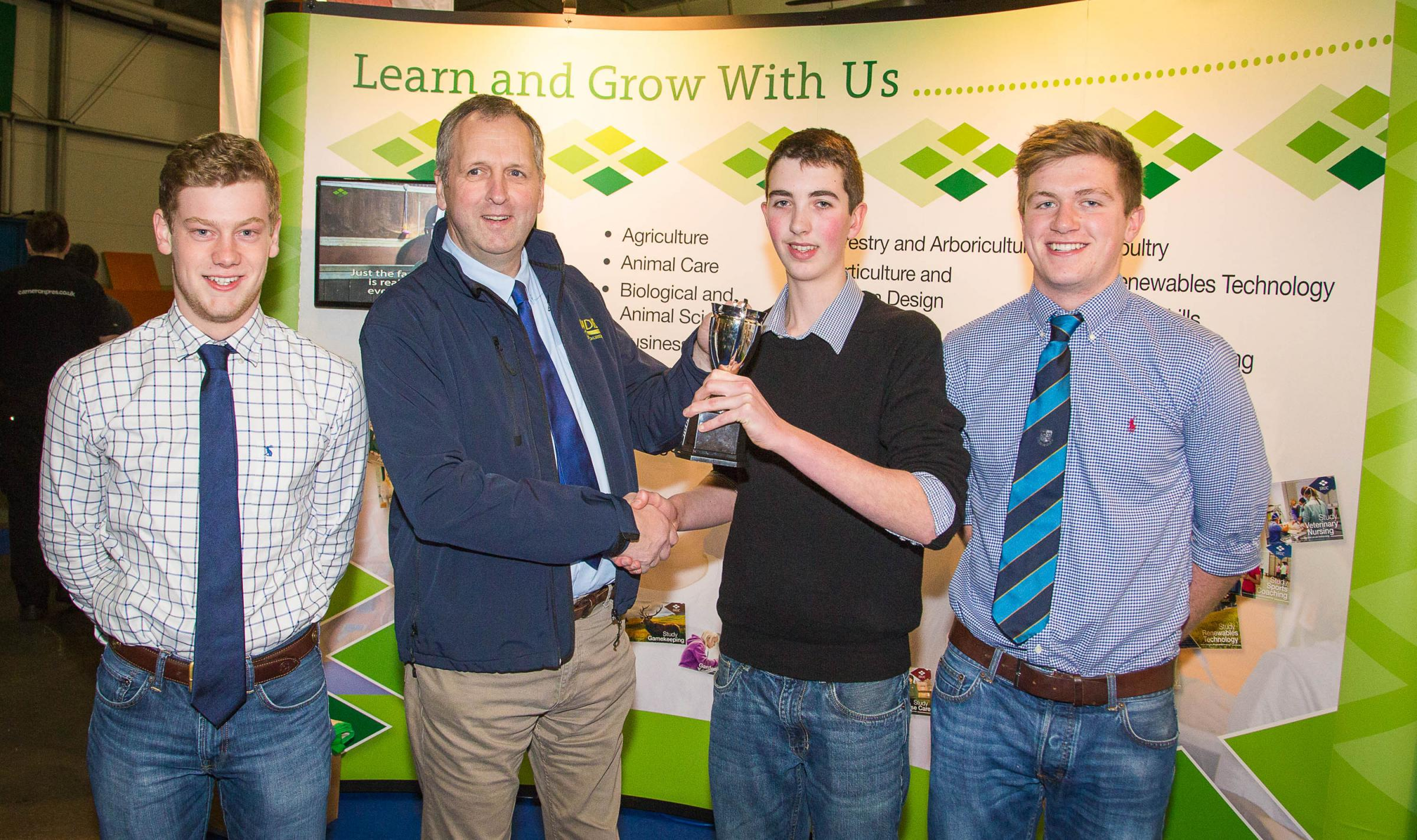 Three of the jubilant winning team from SRUC's Barony Campus receive the 2016 Mains of Loirston Winter Wheat Challenge trophy from Gavin Dick, Scotland Manager, AHDB Cereals and Oilseeds.