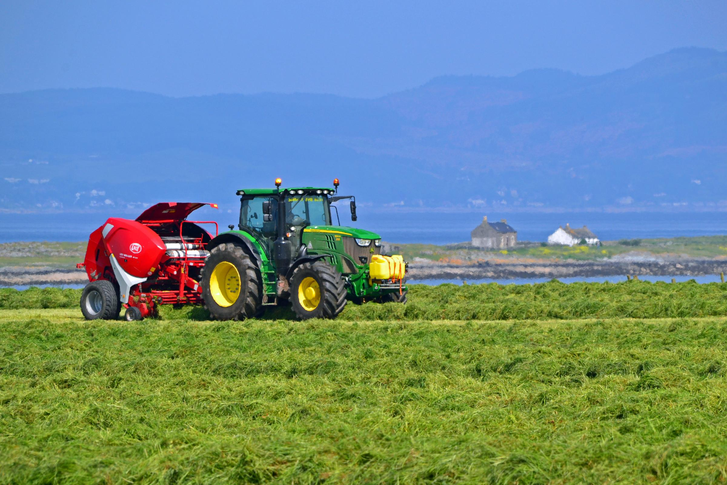 REYNOLDS TEAM baling at Wee Kilmory Farm, Isle of Bute, for Ian Dickson, with St Ninians Bay in the background