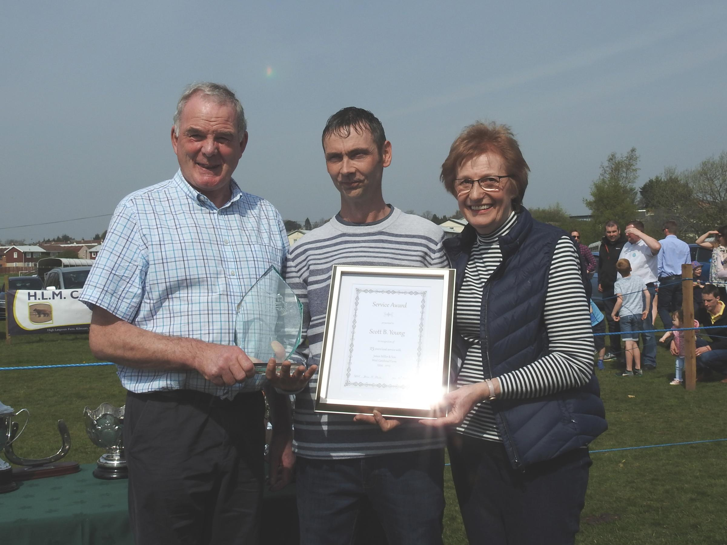 SCOTT YOUNG has been presented with an award for 25 years service to the Miller family of West Gatehead Farm, Kilmarnock. He is pictured here, receiving his award from Jim and Nanette Miller, at last weekend's Kilmaurs Show
