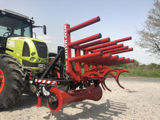 The front-mounted holder from Darren Bailey, the Grizzly Wrap Master, carries a much needed store of net and wrap for almost non-stop baling, and folds forward to allow the rolls to be easily and safely removed