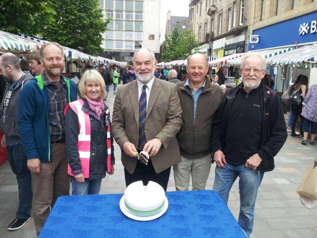 Councillor Murray Lyle, leader of Perth and Kinross Council, and a local farmer, cutting the cake to celebrate Perth Farmers' Market 20th anniversary, flanked by Andrew Scarlett, Adeline Watson, David Burberry, and Hamish Coutts